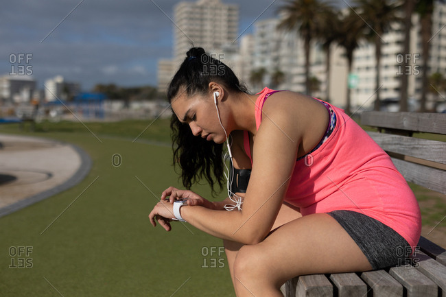 Side view of female jogger using smart watch in the park