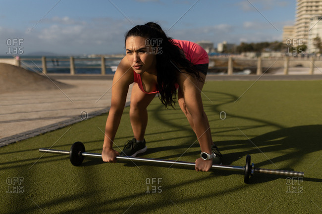 Young female jogger exercising with barbell in the park