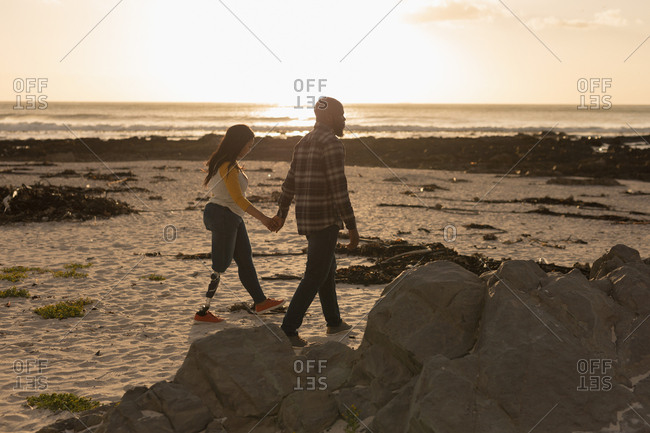 Couple holding hands and walking on beach during sunset