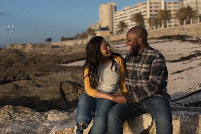 Happy couple sitting on beach