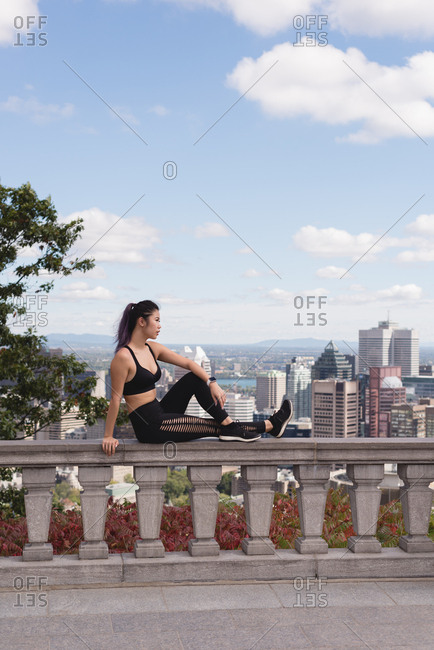 Female jogger relaxing on railing on a sunny day