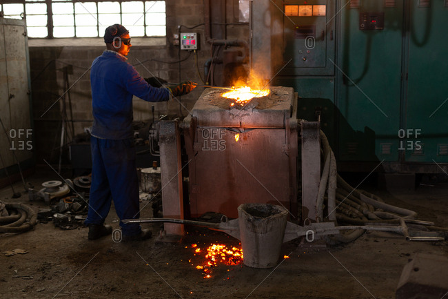 Male worker molting metal in foundry workshop