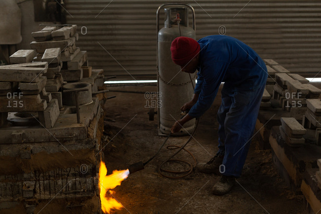 Worker heating furnace with flaming torch in foundry