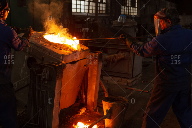 Male workers working in foundry workshop