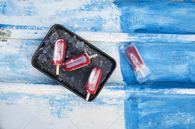 Red popsicles on a tray and one in a wrapper