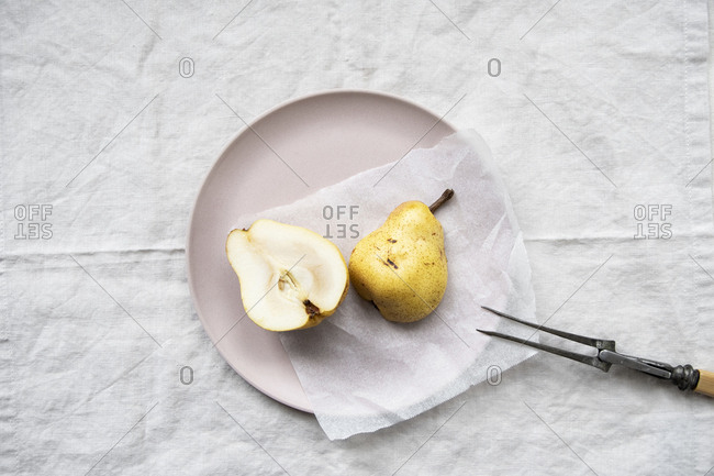 Pear sliced in half on a pink plate