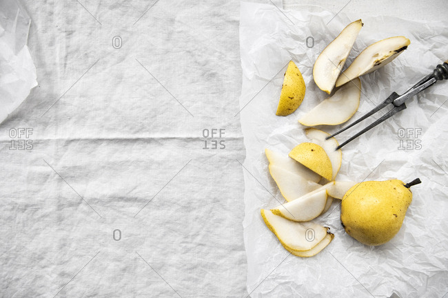 Sliced and whole pear on parchment paper