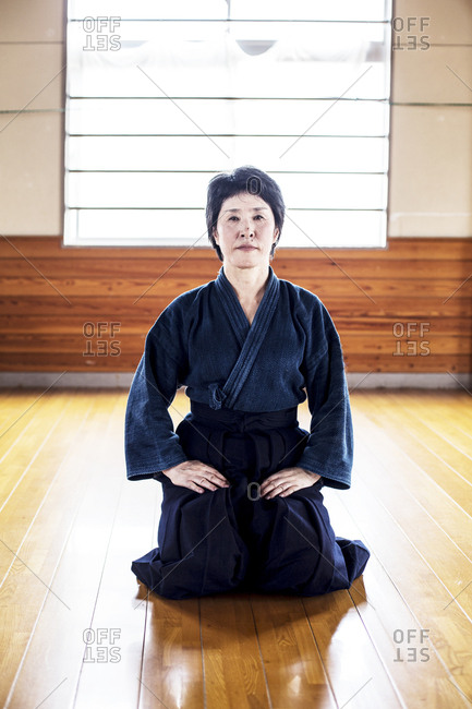 Female Japanese Kendo fighter kneeling on wooden floor, looking at camera.
