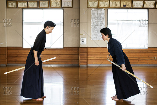 Female and male Japanese Kendo fighters standing opposite each other on wooden floor, bowing and greeting.