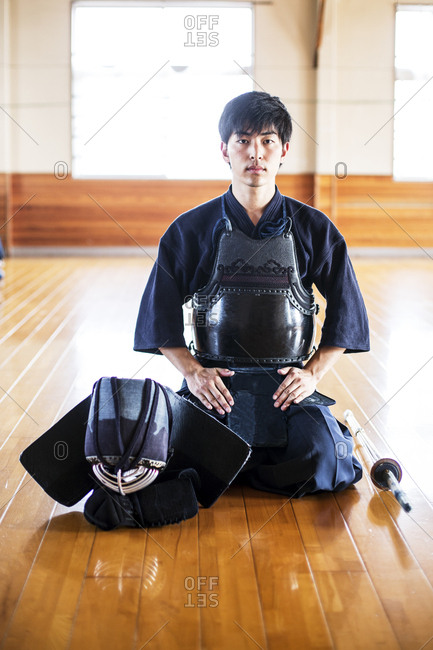 Male Japanese Kendo fighter kneeling on wooden floor, looking at camera.