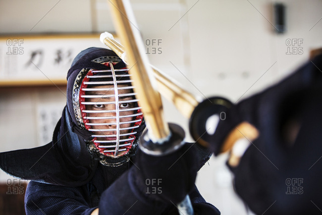 Close up of Japanese Kendo fighter wearing Kendo mask in combat pose.