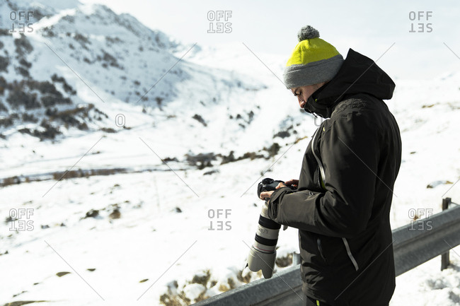 Adult man in black outfit with a Camera in snowy Mountains