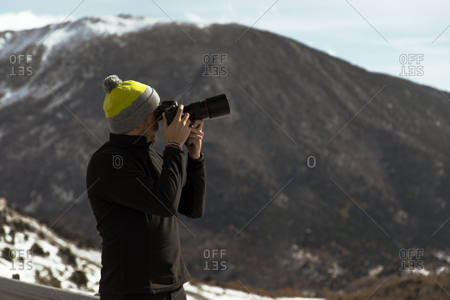 Adult man in black outfit taking photo of snowy mountains in Andorra