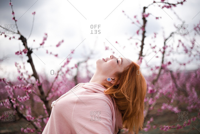 Redheaded woman in front of blossoming tree looking up