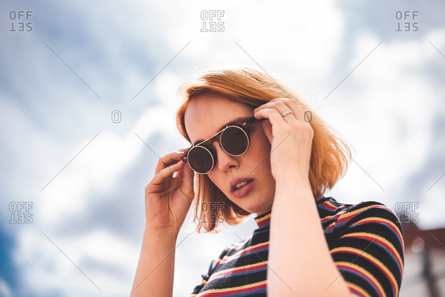 Young red haired woman putting on sunglasses