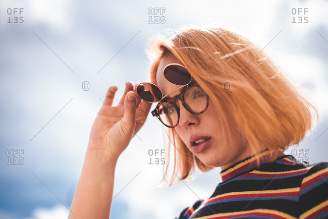 Young red haired woman flipping up sunglasses