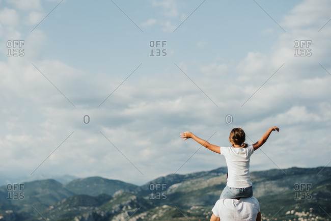 Girl with outstretched arms sitting on father's shoulders looking at scenic view of the mountains