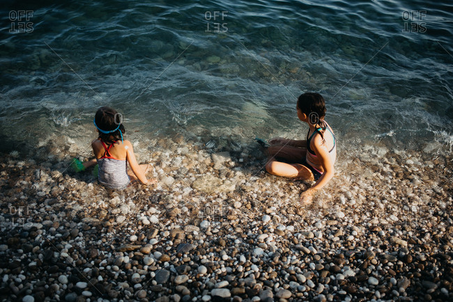Girls sitting in shallow water of river