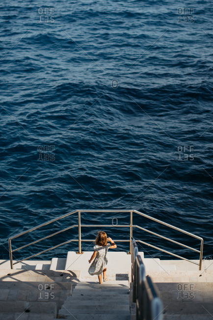 Girl walking down stairs leading to the ocean