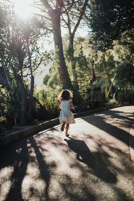 Back view of girl running down a country lane through natural area