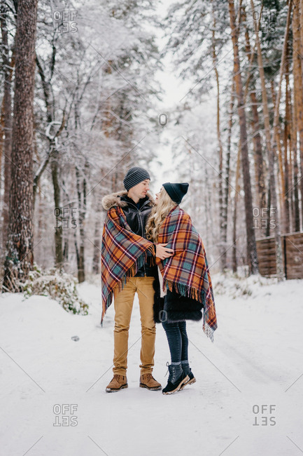 married beautiful couple hugging looking at each other in the winter forest throwing warm checkered blanket