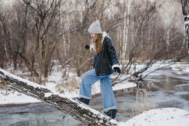 beautiful woman goes and balances the tree and looks at his feet. on the background of winter forest and river