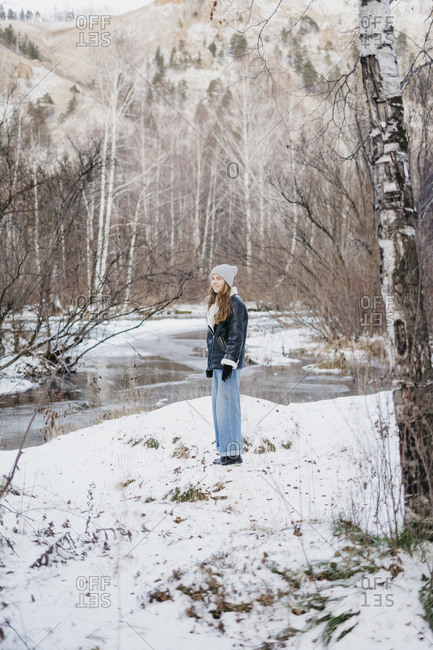 beautiful woman standing on freshly fallen snow. on the background of winter forest and river
