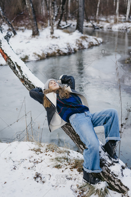 beautiful woman lies on a tree and looks at the sky. on the background of winter forest and river