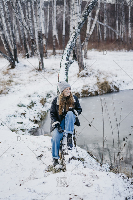beautiful girl sitting on a tree background of a winter forest and river