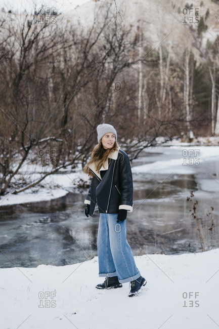 beautiful girl posing against the backdrop of the winter forest and the river