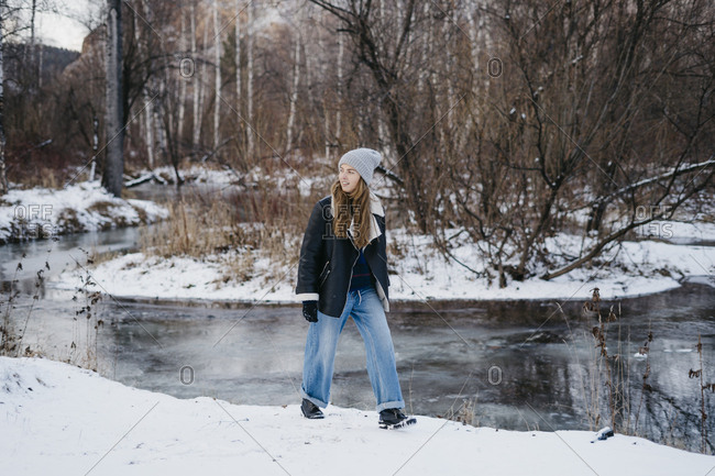 beautiful girl goes and looks the nature against the background of the winter forest and the river