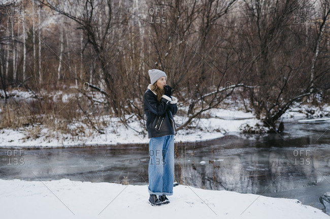 beautiful girl warm hands on the background of the winter forest and the river