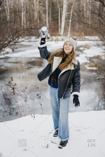 beautiful girl throws a snowball at a friend in the background of winter forest and river