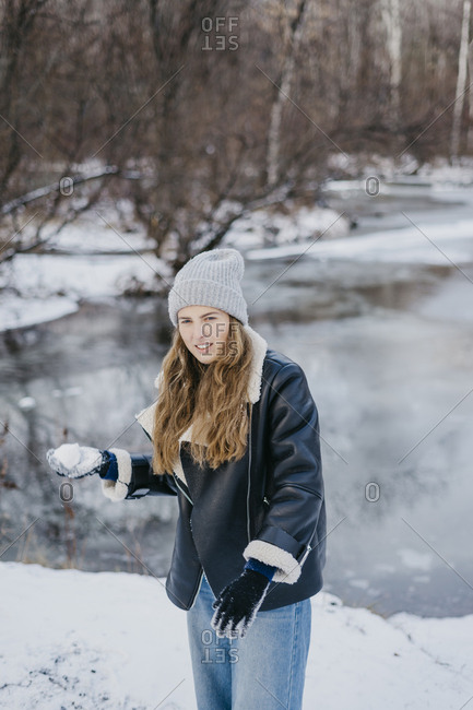 beautiful girl with a snowball in hand against the background of a winter river