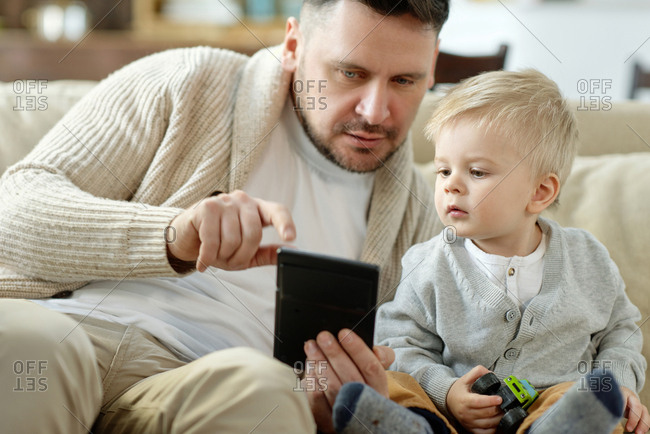 Charming little boy looking curiously at portable gadget in hands of father sitting on couch