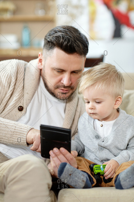 Adult handsome man cuddling on couch with little curious boy while watching device together