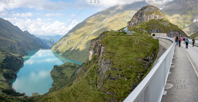 Stausee Mooserboden - September 5, 2018: Kaprun, Austria - September 5, 2018. Tourists crossing the dam wall of the high mountain reservoir Mooserboden Stausee in Kaprun.