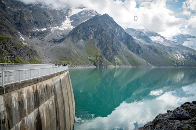 Kaprun, Austria - September 5, 2018. Tourists crossing the dam wall of the high mountain reservoir Mooserboden Stausee in Kaprun.