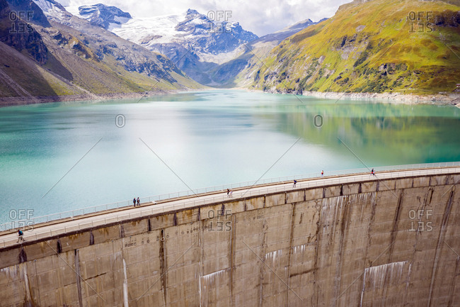 Kaprun, Austria - September 6, 2018. Tourists crossing the dam wall of the high mountain reservoir Mooserboden Stausee in Kaprun.