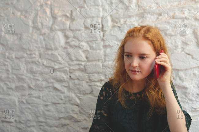 Redhead woman talking on mobile phone in cafe