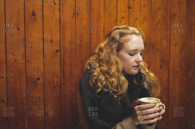 Redhead woman holding a coffee mug in cafe