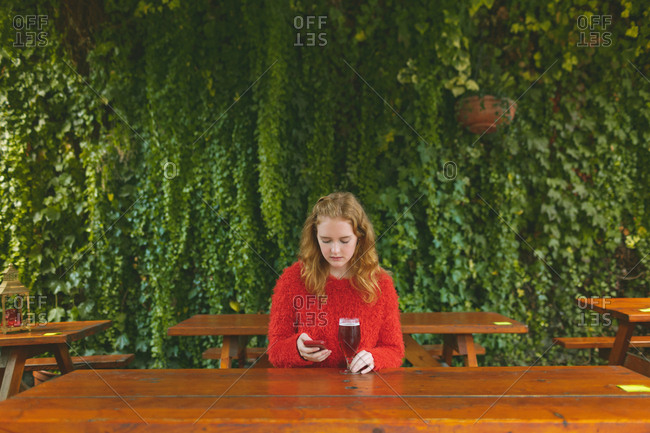 Redhead woman using mobile phone while having beer in outdoor cafe