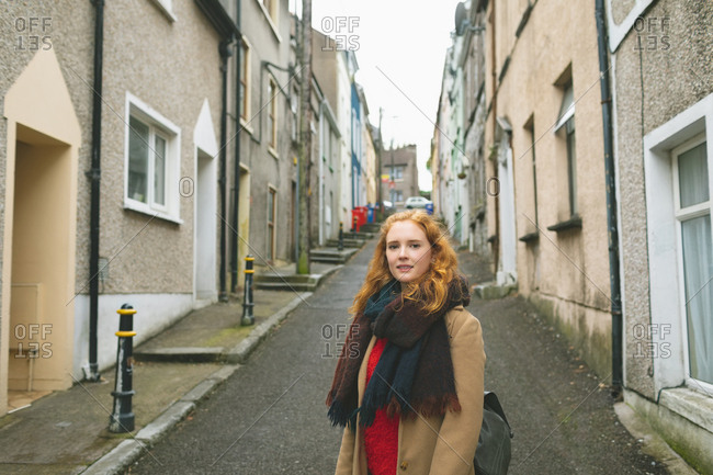 Redhead woman standing on alley street
