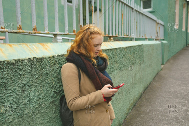 Redhead woman using mobile phone in a alley
