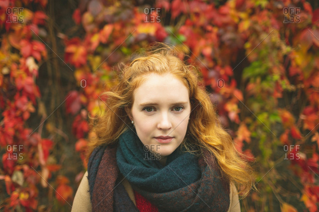 Redhead woman standing against plant creeper during autumn