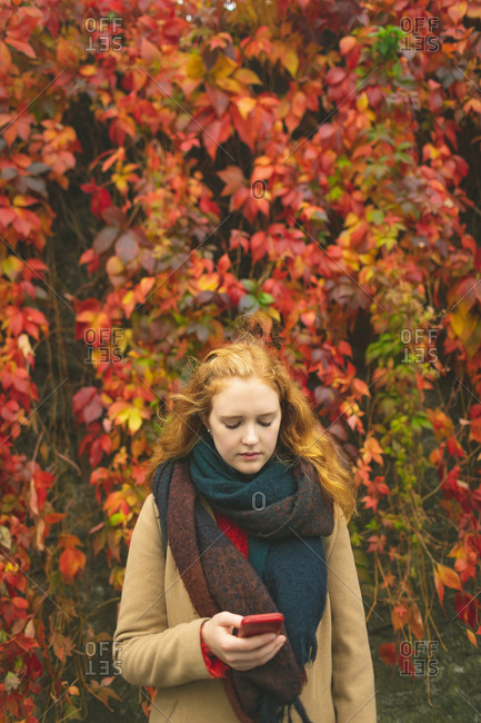 Redhead woman using mobile phone against plant creeper during autumn