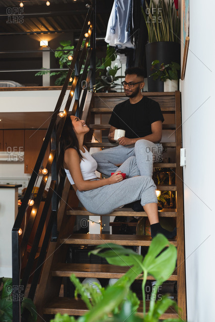 Couple interacting with each other while having coffee in stairs at home