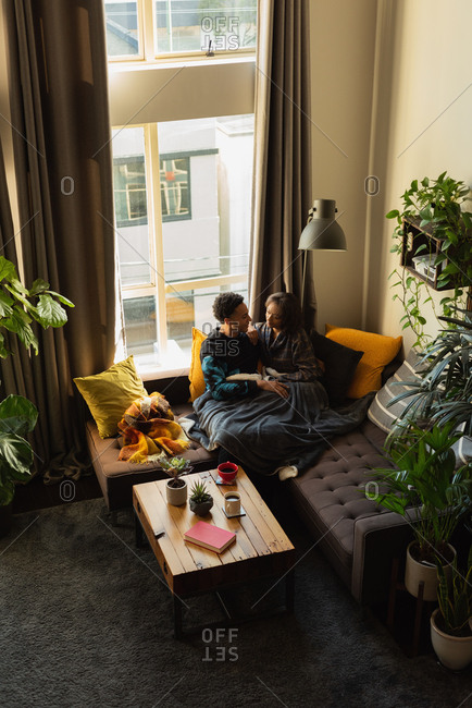 Couple interacting with each other on sofa in living room at home