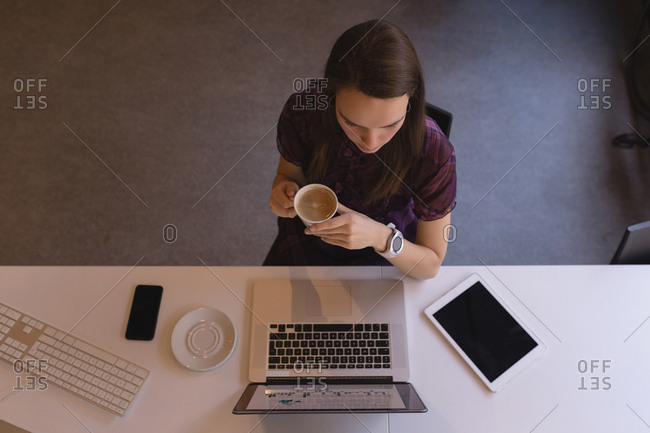 Beautiful businesswoman having coffee while using laptop in office