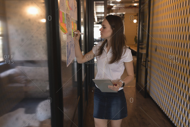 Beautiful female executive writing on graph in office